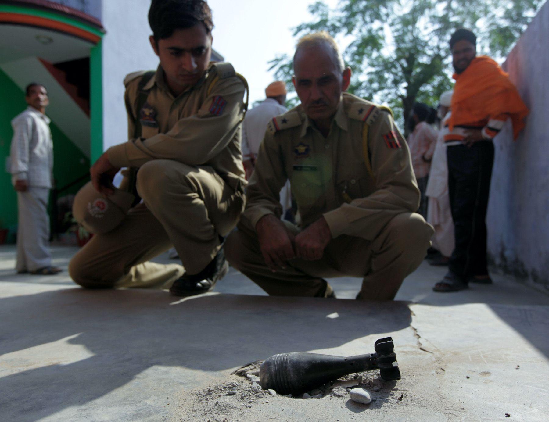 Indian policemen looking at a mortar shell